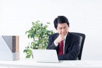 パソコンを見て顔をしかめる男性